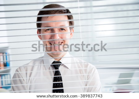 Handsome young businessman at the office blinds. - stock photo