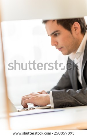 Handsome young businessman concentrating on his work as he sits at his desk navigating the internet on his laptop computer while reading the screen, profile view. - stock photo