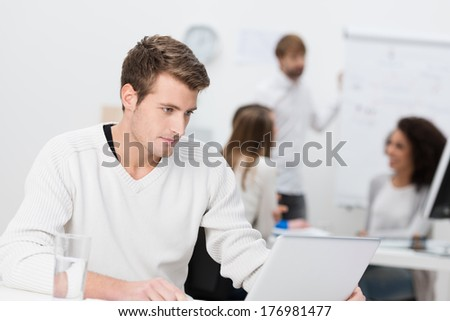Handsome young businessman concentrating on his work sitting at his desk using a laptop computer - stock photo