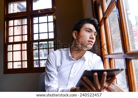 handsome young businessman drinking coffee in cafe and using tablet computer - stock photo