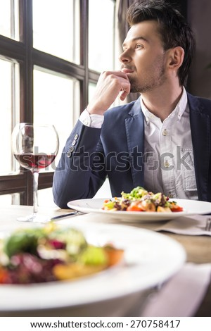 Handsome young businessman eating during a business lunch in restaurant. - stock photo