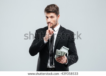 Handsome young businessman holding money and showing silence sign over white background - stock photo