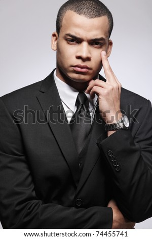 Handsome young businessman in black suit. - stock photo