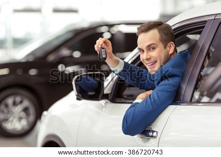 Handsome young businessman in classic blue suit is smiling, looking at camera and showing car keys while sitting in car in a motor show - stock photo