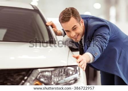 Handsome young businessman in classic blue suit is smiling while examining car in a motor show - stock photo