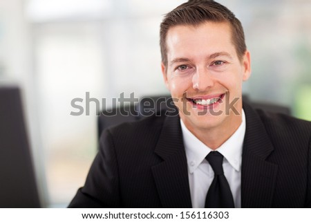 handsome young businessman in office looking at the camera - stock photo