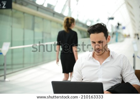 handsome young businessman in public station working on computer in wifi area while waiting for his aircraft or train - stock photo