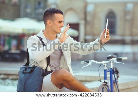 Handsome young businessman is relaxing in the city and waving to camera of his digital tablet. He is sending photo messaging or having a video call. - stock photo
