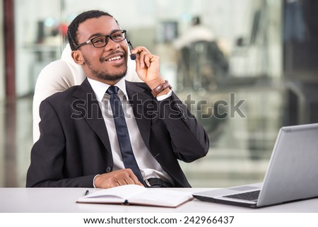 Handsome young businessman is taking a call on a headset as he deals with queries at the customer support call centre. - stock photo