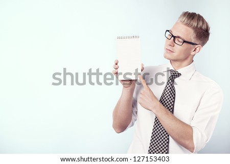 Handsome young businessman pointing finger at blank notebook with space for text while looking at it, isolated. - stock photo