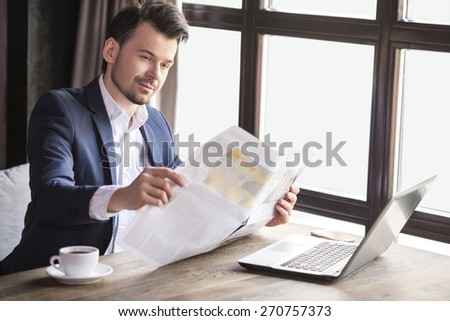 Handsome young businessman reading newspaper with cup of coffee in restaurant. - stock photo