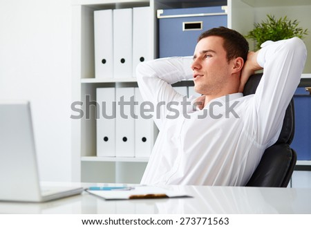 Handsome young businessman resting in office - stock photo