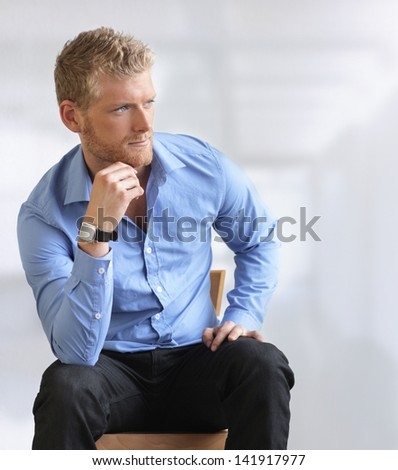 Handsome young businessman sitting - stock photo