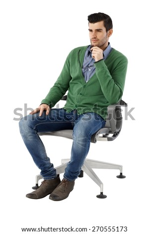 Handsome young businessman sitting and thinking in swivel chair over white background, looking away. Full size. - stock photo