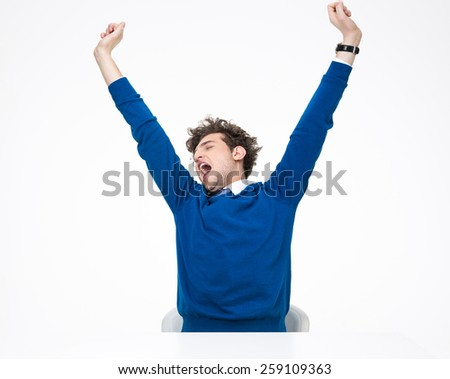 Handsome young businessman sitting at the table and stretching - stock photo