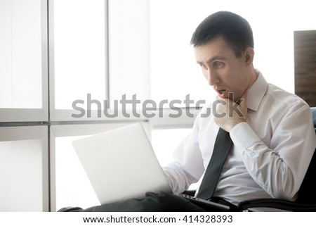 Handsome young businessman sitting in his office using laptop. Caucasian business man in formal wear looking at computer screen with shocked facial expression. Copy space - stock photo