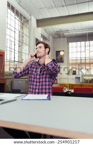 Handsome young businessman sitting talking on the phone in a large bright airy office, low angle view across the desk - stock photo