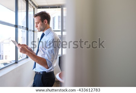 Handsome young businessman standing in his office using a digital tablet, with the view partially obscured by his office doorway - stock photo