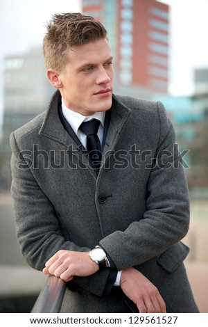 Handsome young businessman standing in the city - stock photo