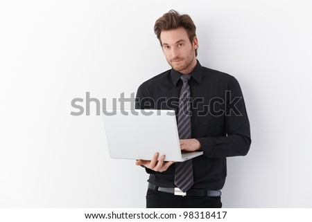 Handsome young businessman standing over white background, holding laptop, smiling. - stock photo