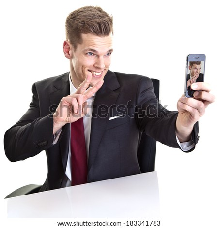 Handsome young businessman taking a selfie with his smartphone - stock photo