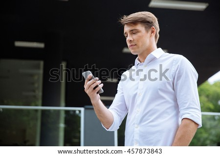 Handsome young businessman using mobile phone outdoors - stock photo
