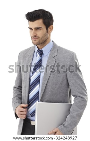 Handsome young businessman walking with laptop computer in hand, looking away. - stock photo