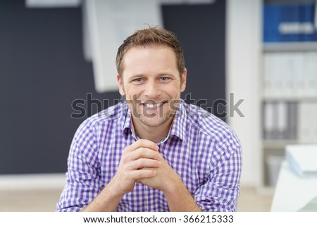 Handsome young businessman with a happy smile sitting in the office looking directly at the camera, informal checked purple shirt - stock photo