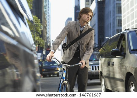 Handsome young businessman with bicycle on busy street - stock photo