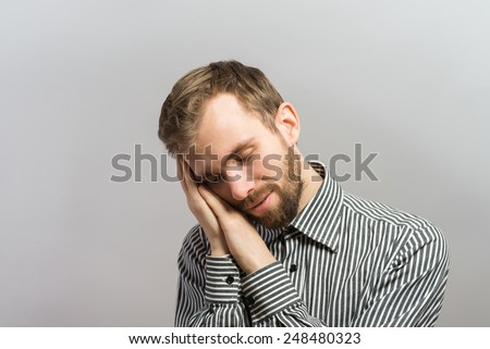Handsome young businessman with hands behind head sleeping on wooden wall - stock photo
