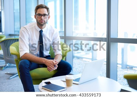 Handsome young businessman with stylish spectacles, sitting in a modern office at a coffee table with takeaway coffee and his laptop - stock photo