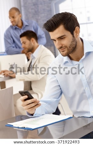 Handsome young businessman working in office, using mobilephone, texting. - stock photo