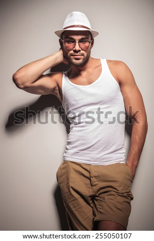 Handsome young casual man holding one hand behind his neck while leaning on a white wall with his hand in pocket. - stock photo