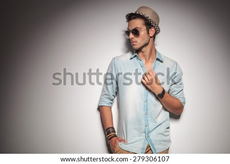 Handsome young casual man looking to his side while holding one hand in his pocket. - stock photo
