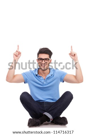 Handsome young casual man sitting and pointing upwards with both hands. he is wearing glasses and smiling to the camera. - stock photo