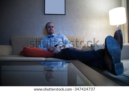 Handsome young caucasian man in a blue shirt and bow tie watching TV - stock photo
