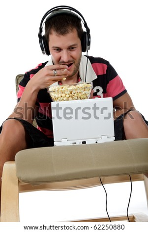 Handsome young caucasian man with headphones  and laptop on sofa listening  music from the internet and eating popcorn. Studio shot. White background. - stock photo