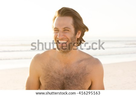 Handsome young cheerful man at beach. Shirtless man at beach enjoying vacation. Portrait of a happy smiling man looking away on the beach.    