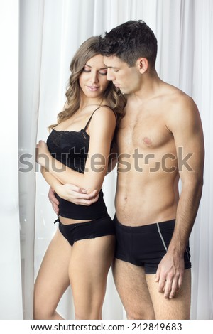 Handsome young couple in love posing in lingerie - stock photo