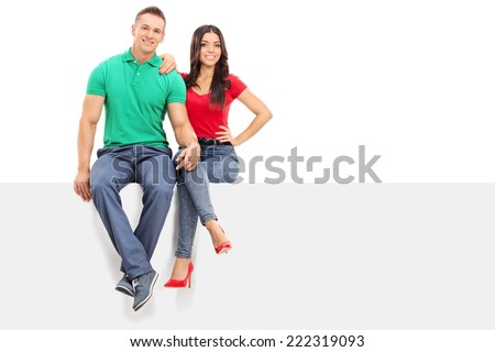 Handsome young couple sitting on a blank panel isolated on white background - stock photo