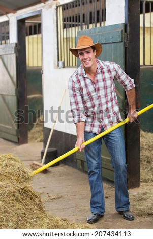 handsome young cowboy working in stable - stock photo