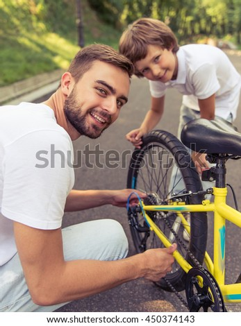 Handsome young dad and his cute little son are riding bikes in park. Both are looking at camera and smiling while father is examining his son's bicycle - stock photo