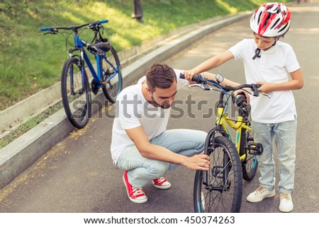 Handsome young dad and his cute little son are riding bikes in park. Father is examining his son's bicycle - stock photo