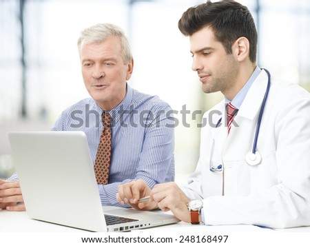 Handsome young doctor explaining results to a senior patient.  - stock photo