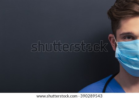 Handsome young doctor in blue medical uniform and mask is looking at camera, standing against blackboard, cropped, close-up - stock photo