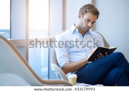 Handsome young entrepreneur writing in his diary while sitting next to a large window, with a cup of takeaway coffee next to him and gentle flare through the window - stock photo