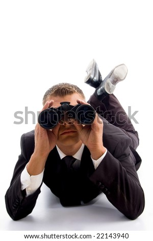 handsome young executive lying on floor and using binoculars with white background - stock photo