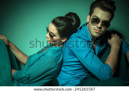 Handsome young fashion man looking at the camera while his lover is leaning on him. - stock photo