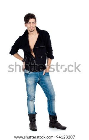 Handsome young fashion model standing and wearing jeans, boots and a black jacket. Isolated on white background. Studio vertical image. - stock photo