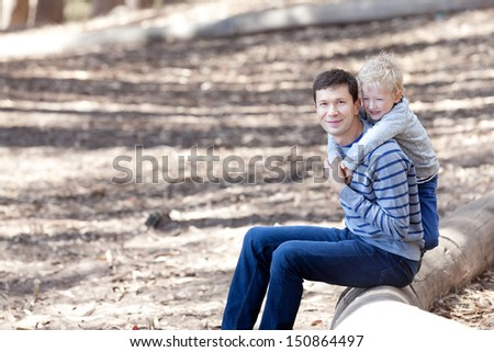 handsome young father and his laughing adorable son spending time together during the hike in the woods - stock photo